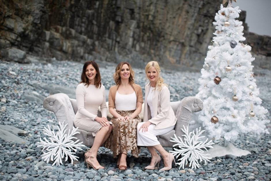 The Ennis Sisters sit on a lounge chair surrounded by Christmas decorations, all of which is situated on rocky shoreline.