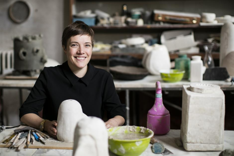 Emma Hart in a studio with a potential sculpture of clay in her hands.