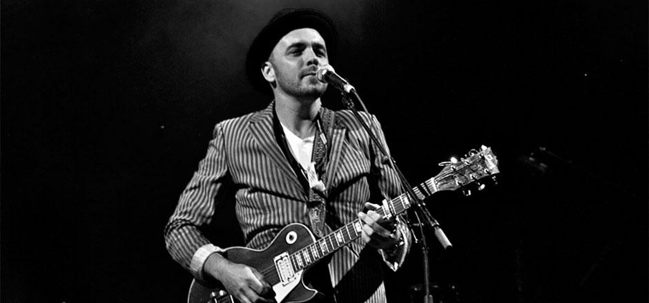Hawksley Workman plays guitar before a mic in a black and white photo.