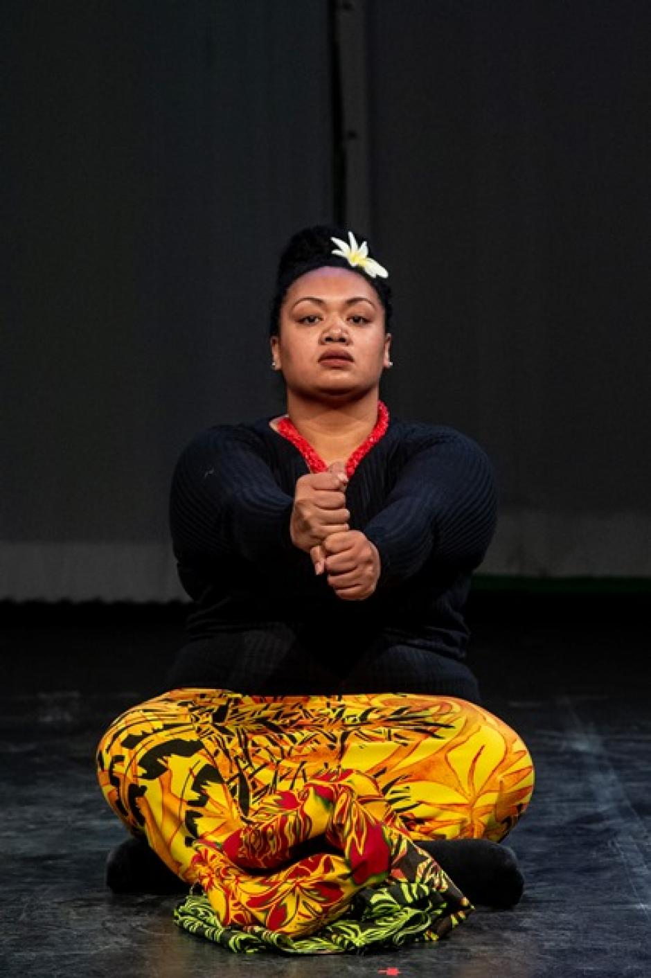 An indigenous woman sits on the ground with her hands in stacked fists held in front of her.