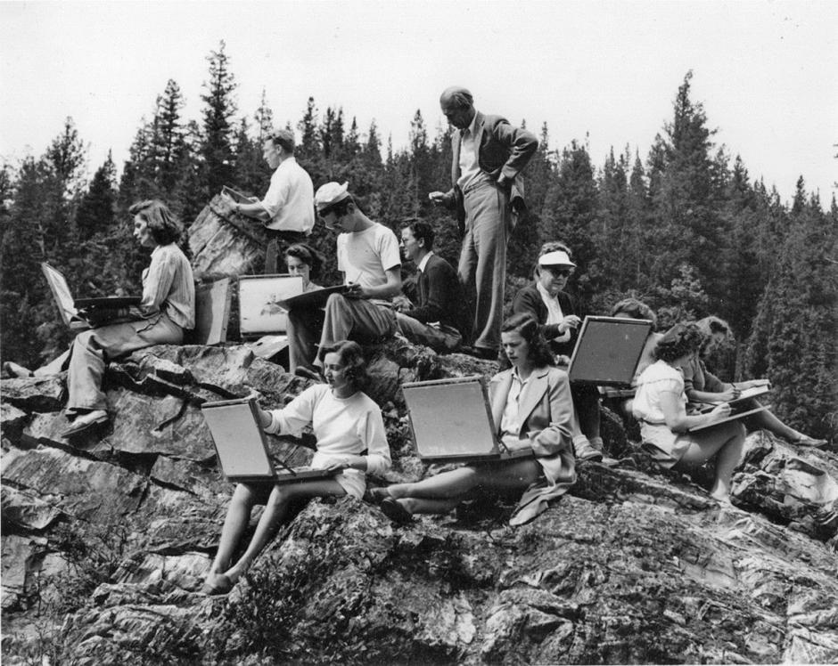 A black and white photo of artists in 1947 sketching seated on a stone hummock.