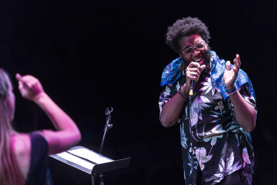 Man in floral shirt sings into held microphone at Banff Centre, Banff National Park, Alberta.