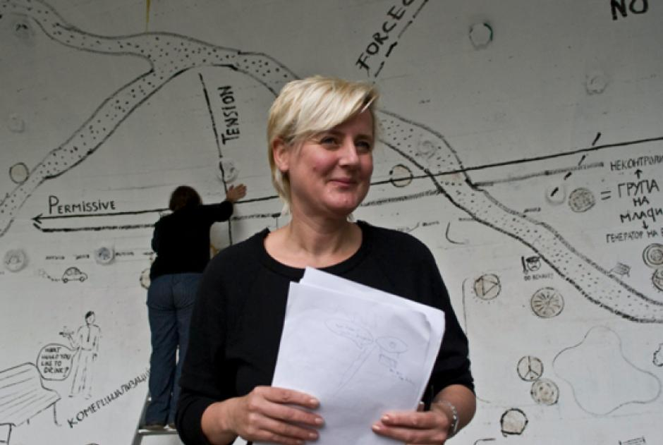 Jeanne van Heeswijk standing in front of an artistically styled map.