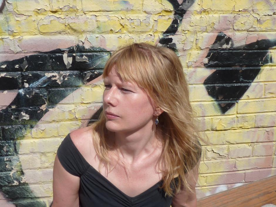 Author Karen Solie looks to her right standing in front of a spray painted wall.