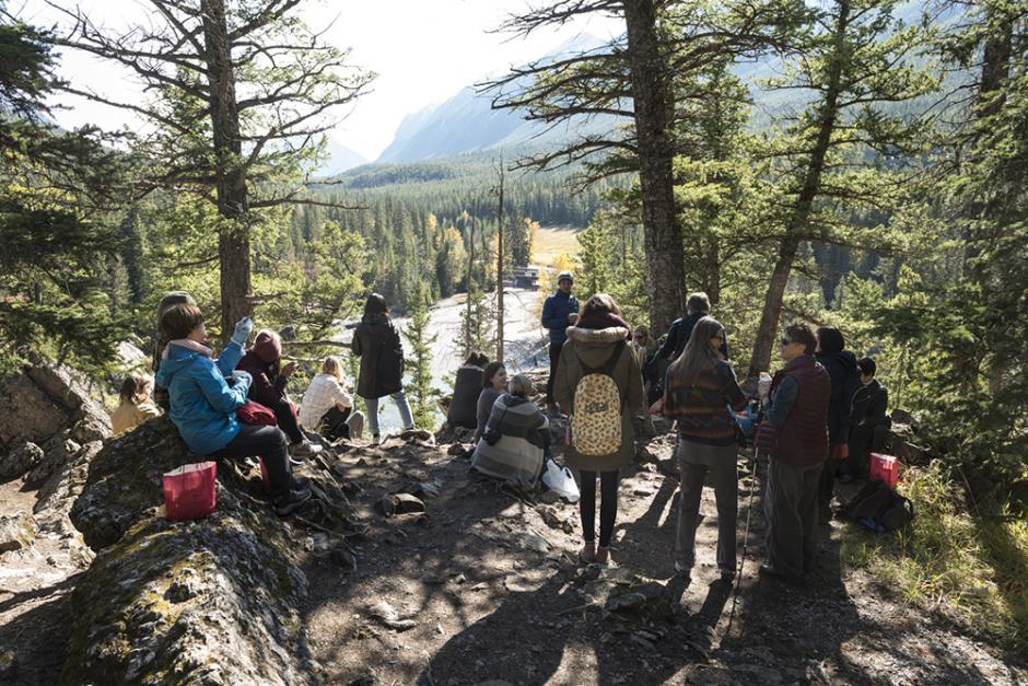 A loosely organized  class wearing backpacks overlooks a river and mountain view.