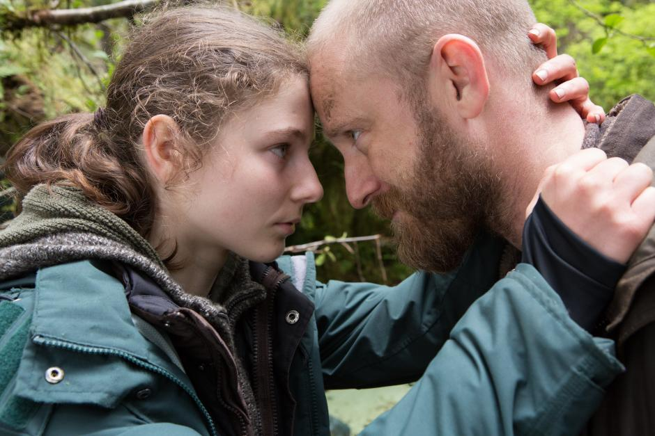 A girl and her father are in a forest holding each other with foreheads pressed together.