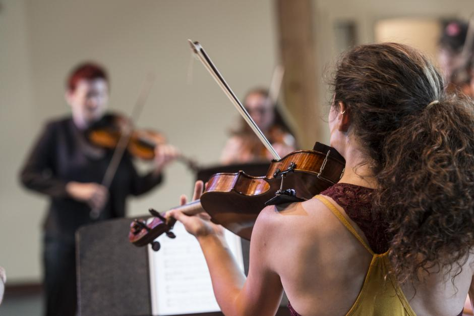 Looking over a young lady's shoulder at the rest of her quartet as she plays violin. Banff Centre, evolution of the string quartet.
