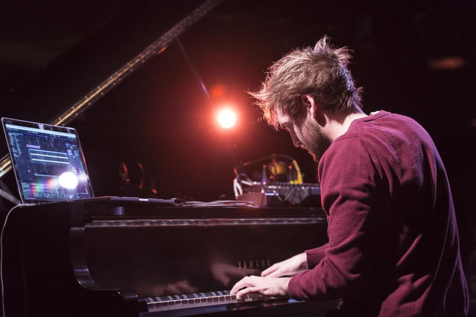 A young man plays the piano with his laptop manipulating the sounds he produces.