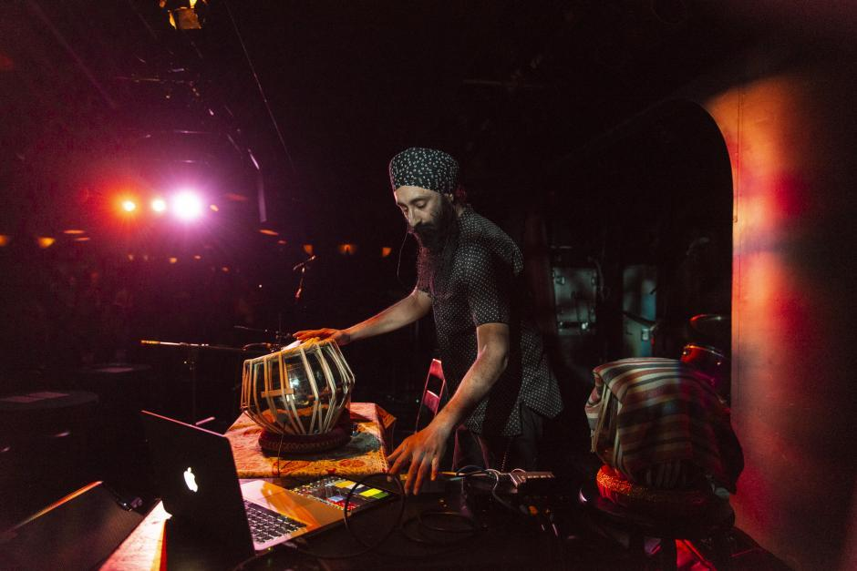 A bearded man stands over a unique drum with electronics beside him.