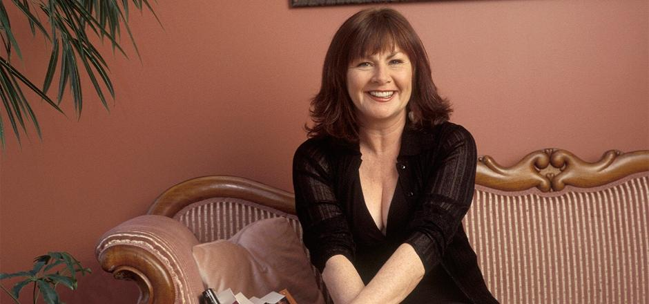 Mary Walsh seated on a pink couch with a pink wall and edge of a plant behind her.
