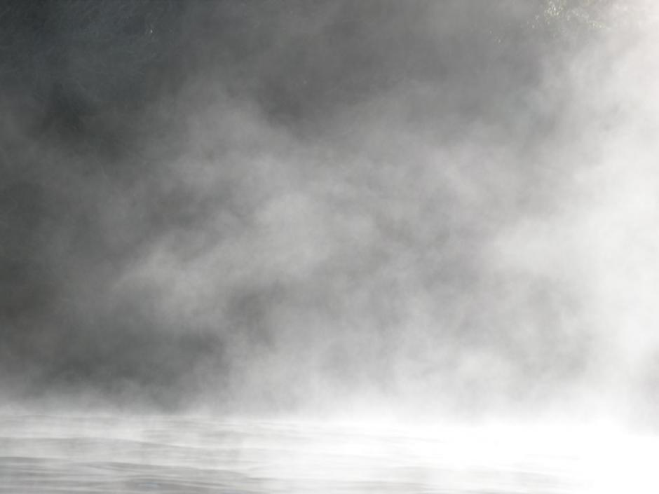 Monochromatic photo of mist travelling over a grey plain.