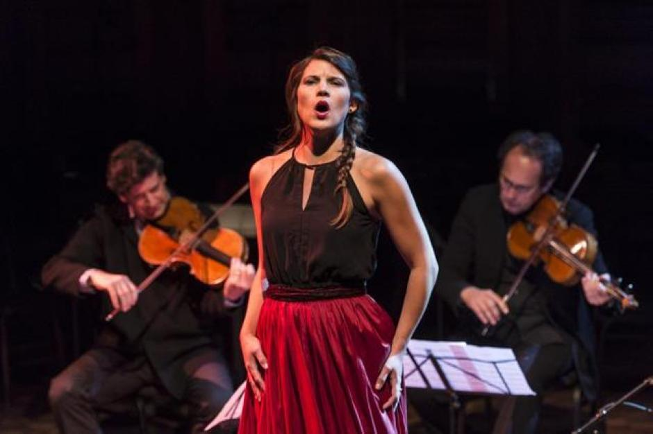 Opera singer performs in front of two violinists.