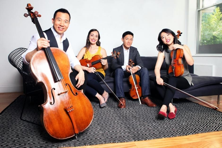 4 musicians of the Parker Quartet, 1 Bassist and three violinists in a casual setting.
