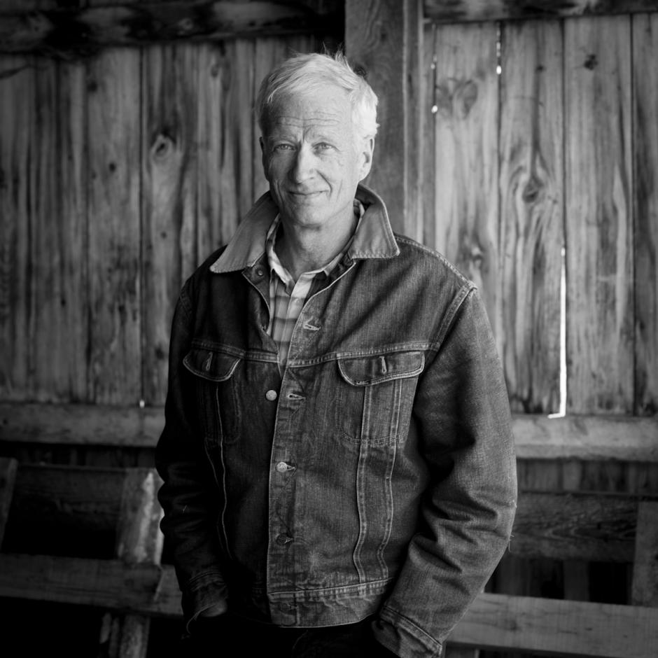 Authour Peter Behrens stands in a barn wearing a jean jacket.