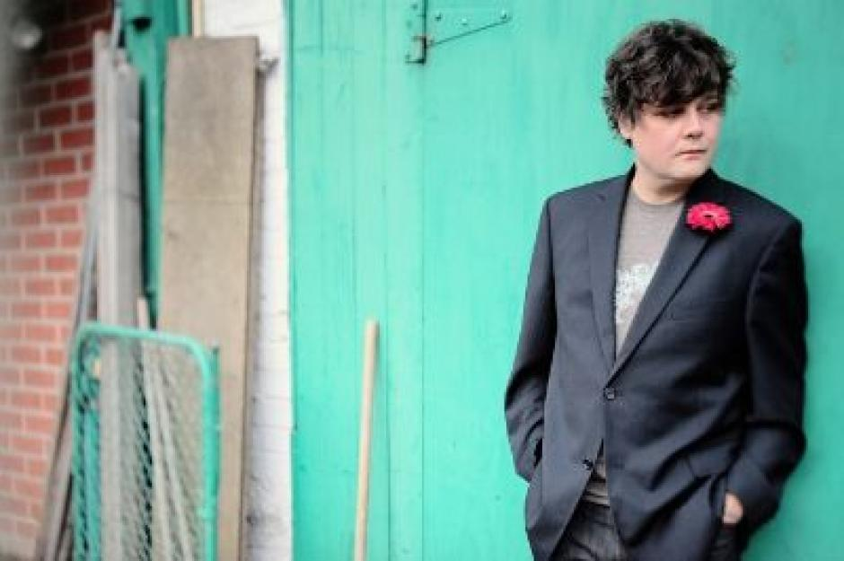 Ron Sexsmith stands in-front of a very large green door with some construction materials leaning against a brick wall to the right.