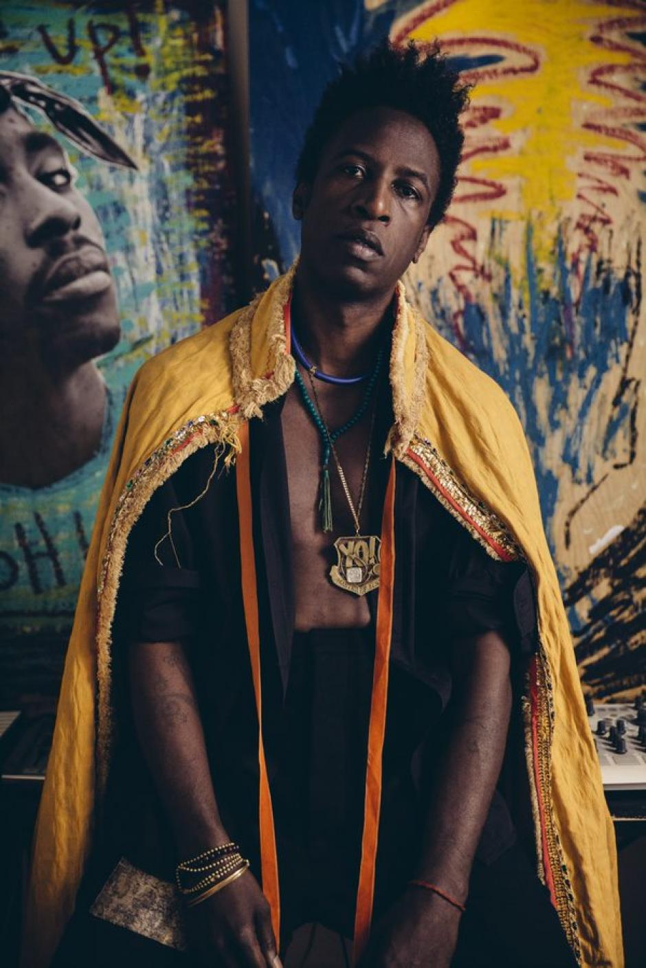 Saul Williams leans back seated with a yellow cap draped over his shoulders and loose fitted black clothes showing his bare chest.