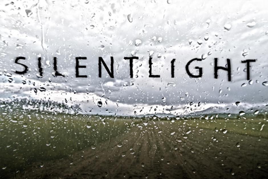 Opera. Silent Light. The words are graphically depicted in black over a rained upon window looking out at a field.