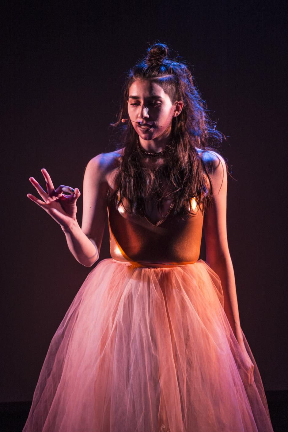 A woman with a headset mic wearing a ballet outfit performs spoken word.