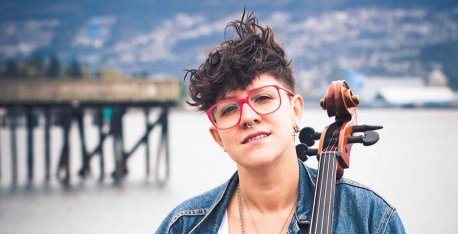 Cris Derksen on a beach seated in front of the pier with her Cello, to perform at Banff Centre 2018.