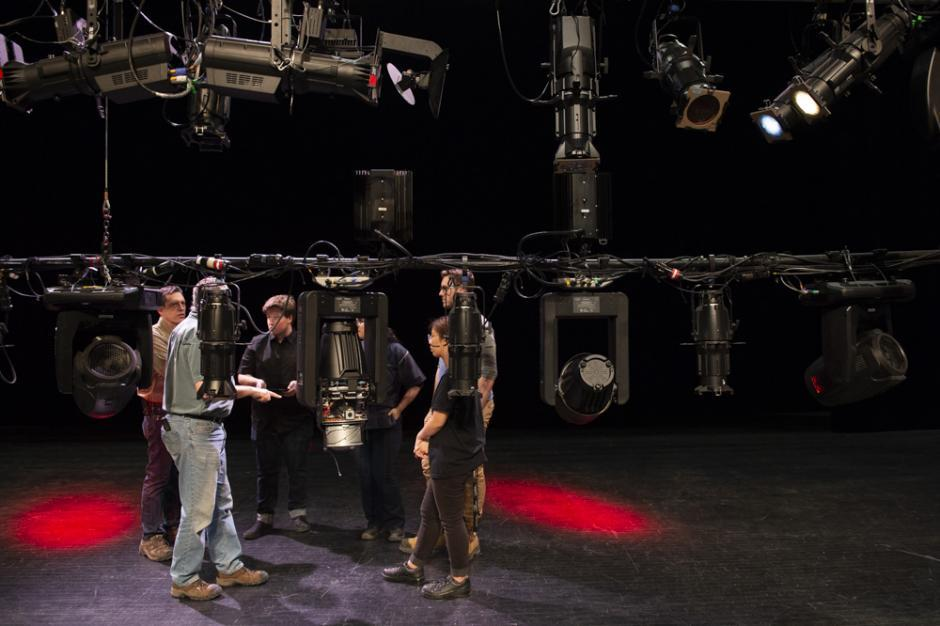 A group gathers backstage behind a lighting rig for a close discussion.