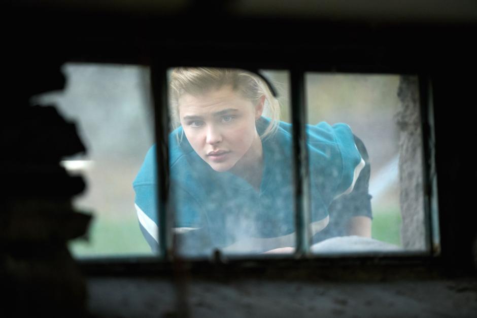 A girl peers into a dark basement through a dirty window.