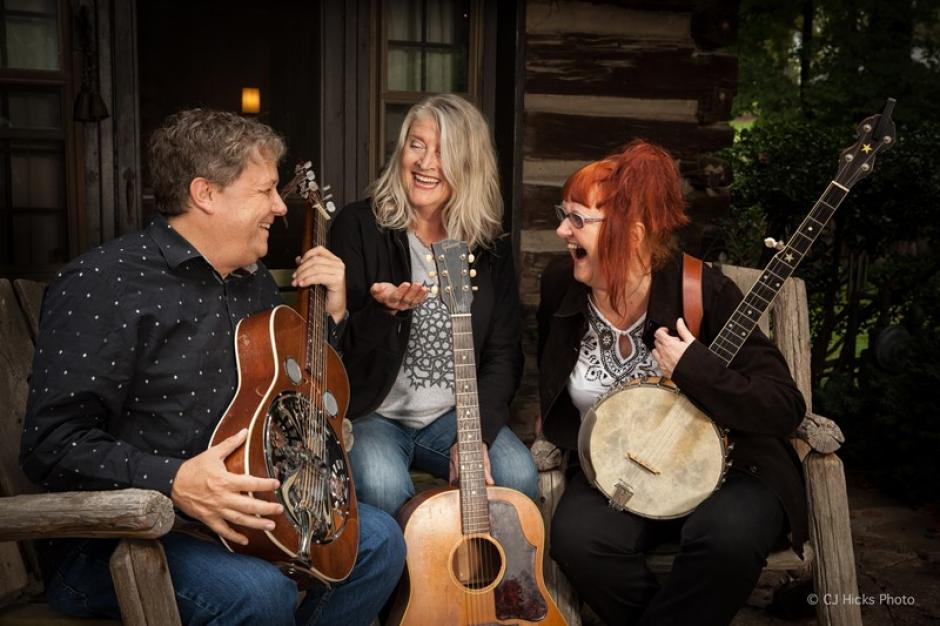 The three new band members laugh on a rustic cabin porch setting holding their instruments.