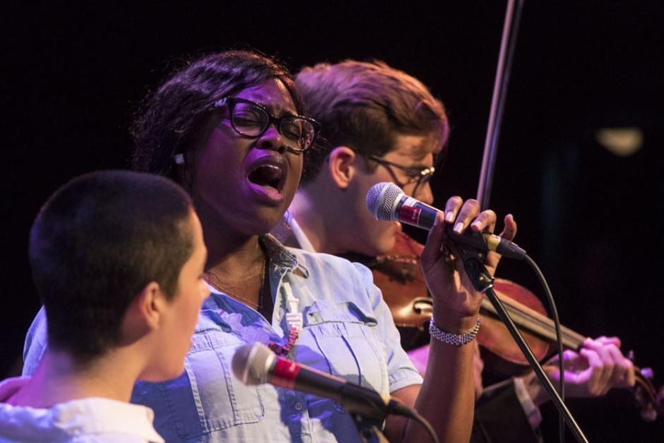Two Banff Centre music participants sing into a microphone with a violinist behind them.
