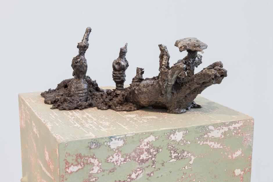 Cold-cast aluminum, resin, soil, rocks, 5 x 14 x 6 inches. The sculpture appears root-like with different protrusions, it is seated atop a faded green and silver burnished cube.
