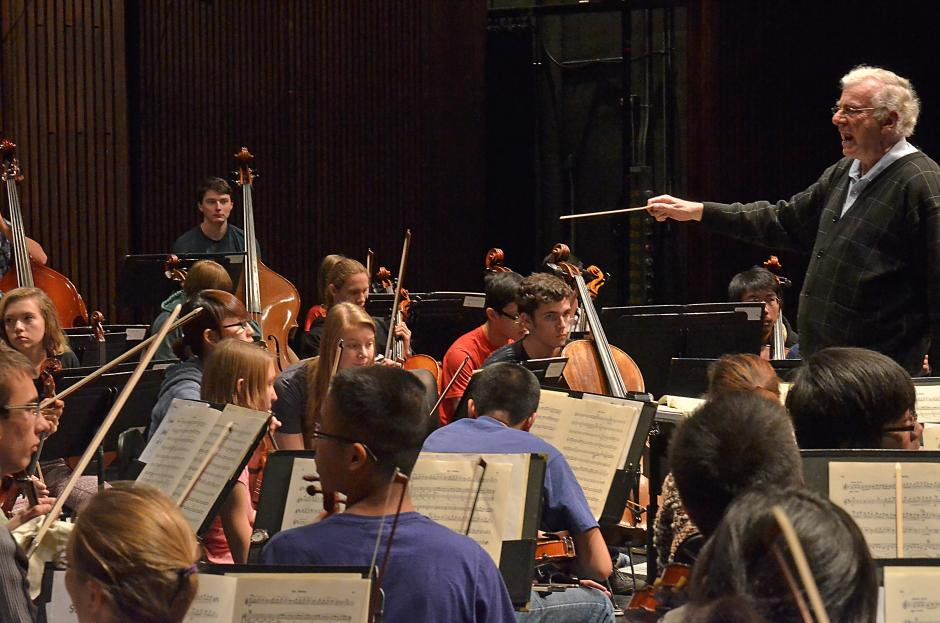 A white haired conductor leads a youth orchestra with his baton.