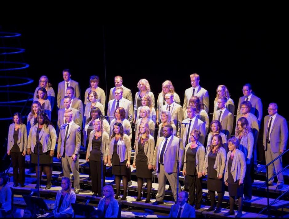 The New West Symphony & Chorus has their choral group in black clothes and beige blazers sings on stage.