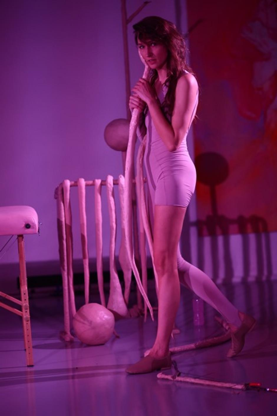 Wearing all saheds of pink with a pink background and pink lighting Kira Nova stands with props.