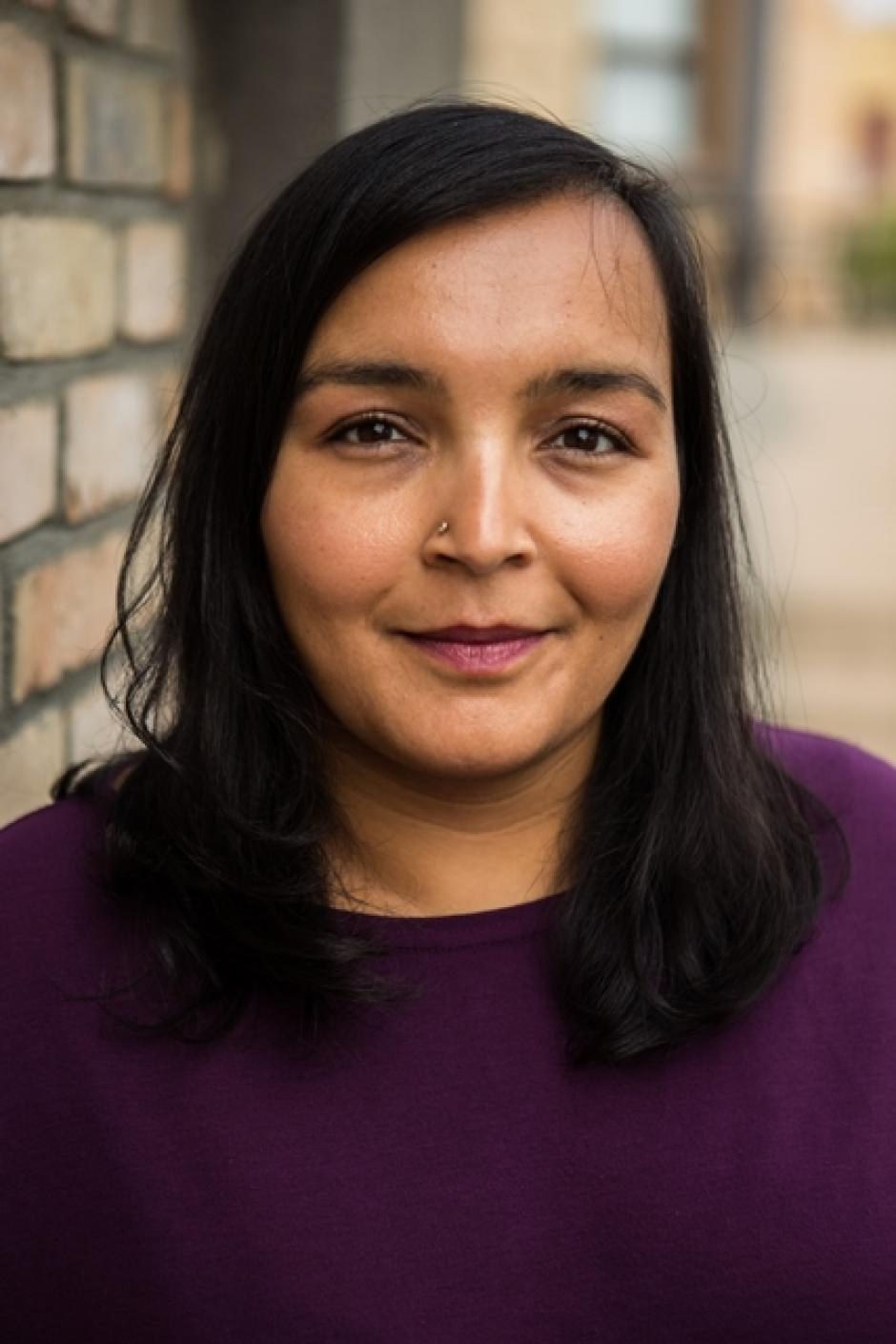 A headhsot of Sharanpal Ruprai wearing a purple sweater and standing in front of a brick wall.