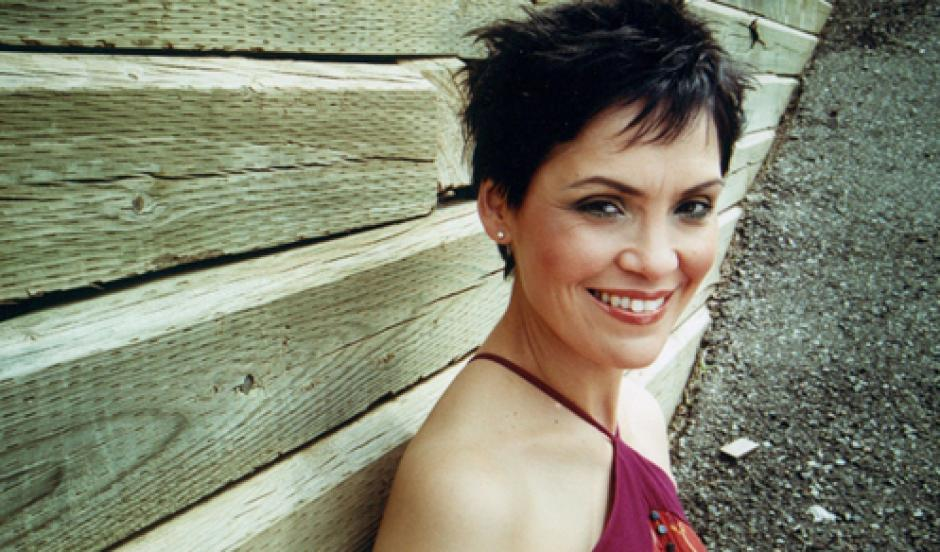 Susan Aglukark smiles in front of a retaining wall of 8x8's