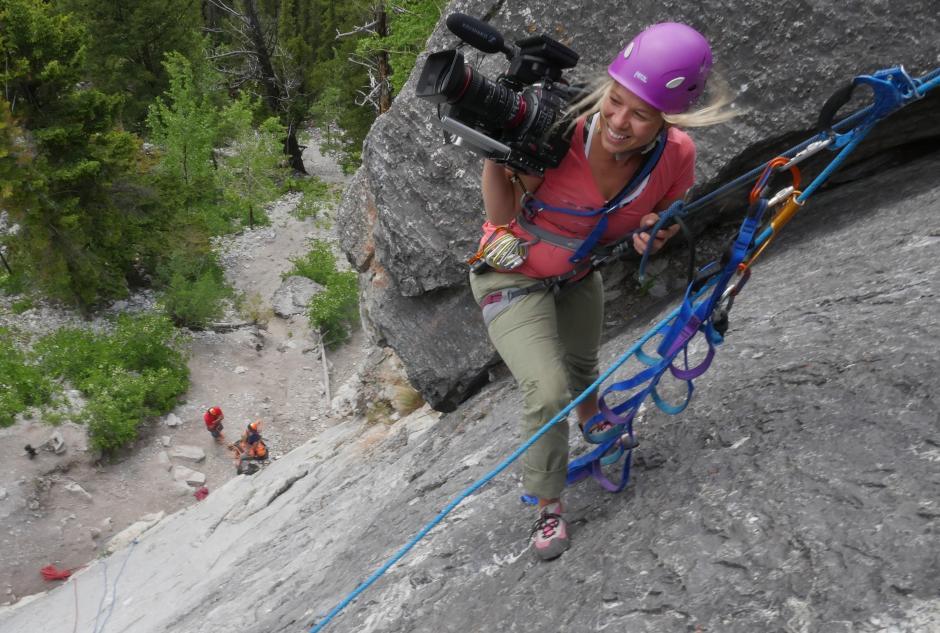 Filmmaker rock climbing with filming equipment