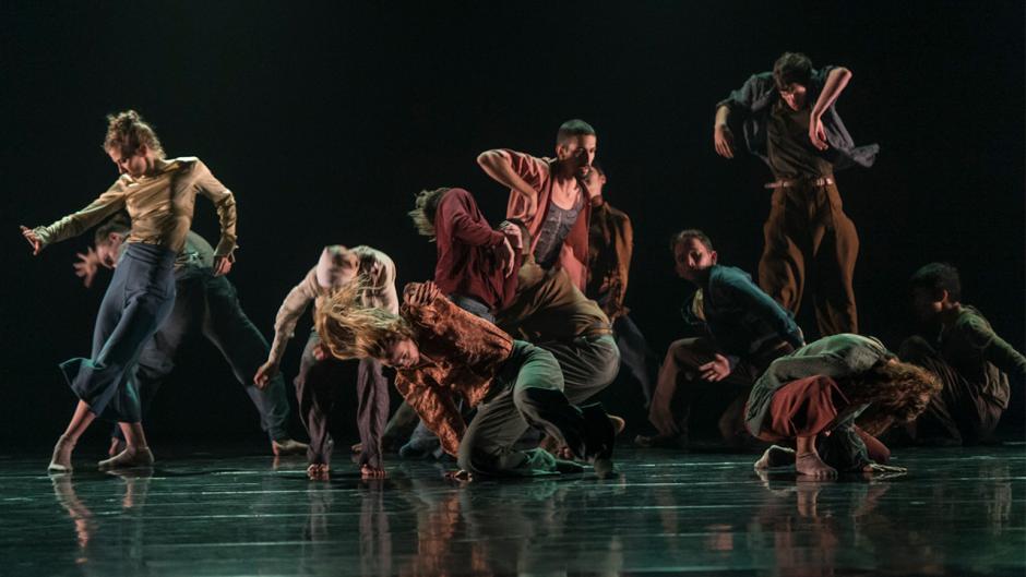 Dancers performing on a dark stage.