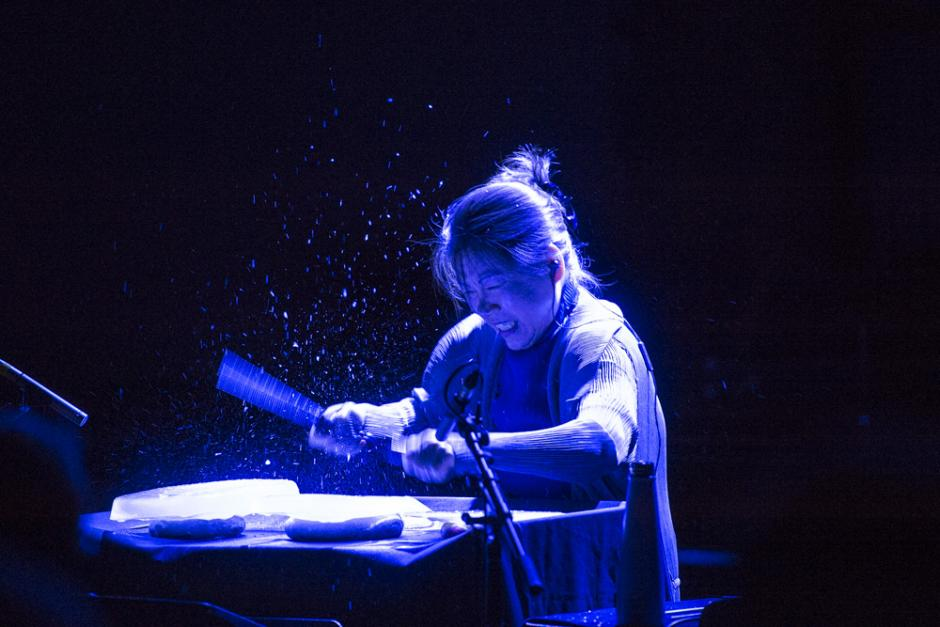A woman lit with an overhead blue light beats a unique drum set.