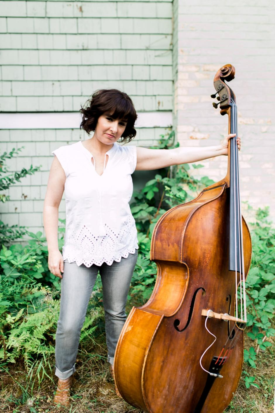 Jodi Proznick stands in front of plants and shrubs while holding her bass with one hand.