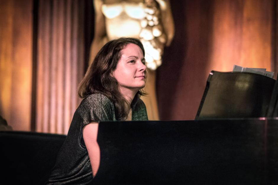 Kris Davis sits at a black piano with pink curtains and a white statue behind her.