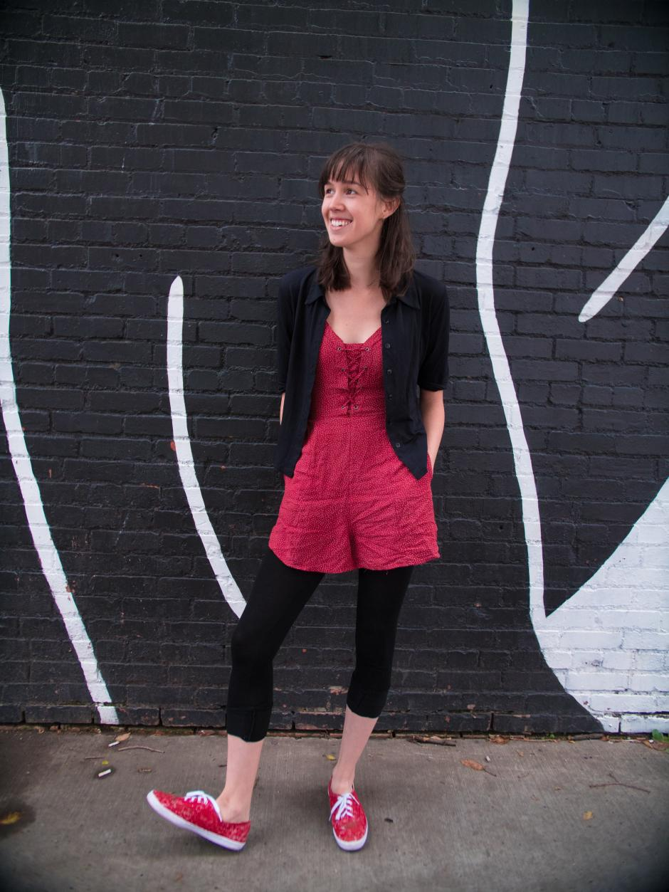 Stephanie stands with her hands in the pockets of her red and white jumper agains a black and white brick wall.