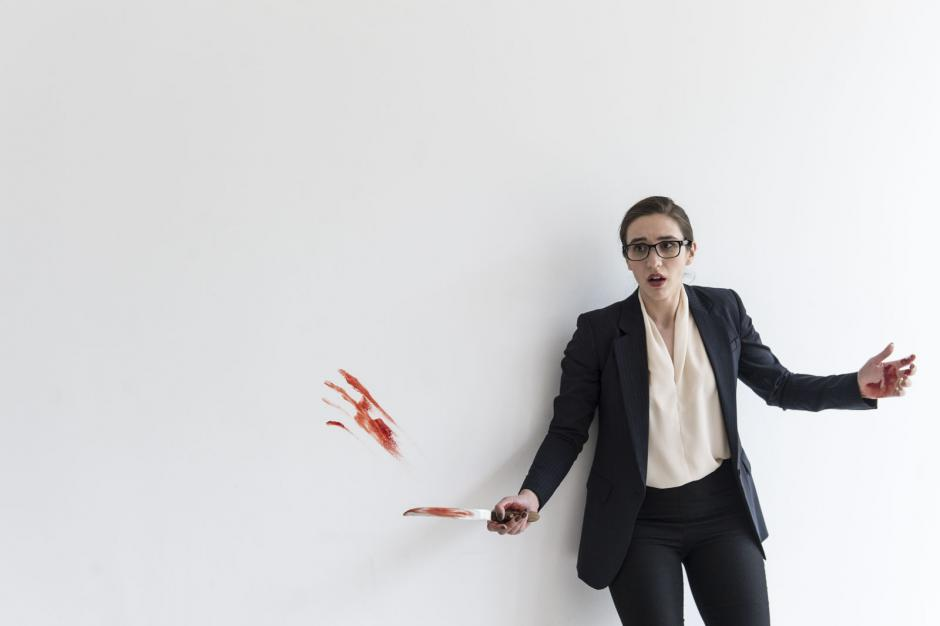 A woman stands surprised against a white background with blood on the knife and wall