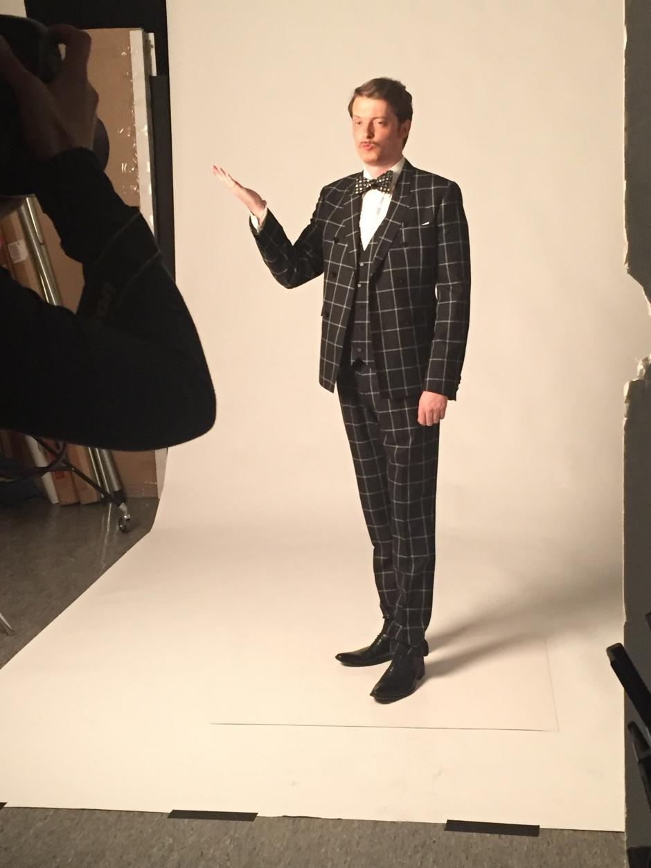 Man in plaid suit poses for camer in photo studio