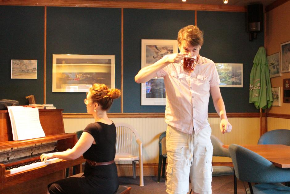 Woman plays piano while standing man takes a drink