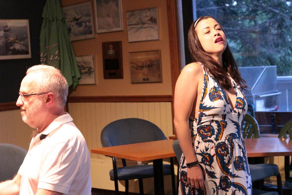 Woman in dress sings while man in white shirt plays piano
