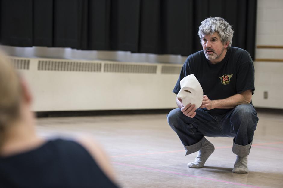 Peter Balkwill crouching and holding a mask