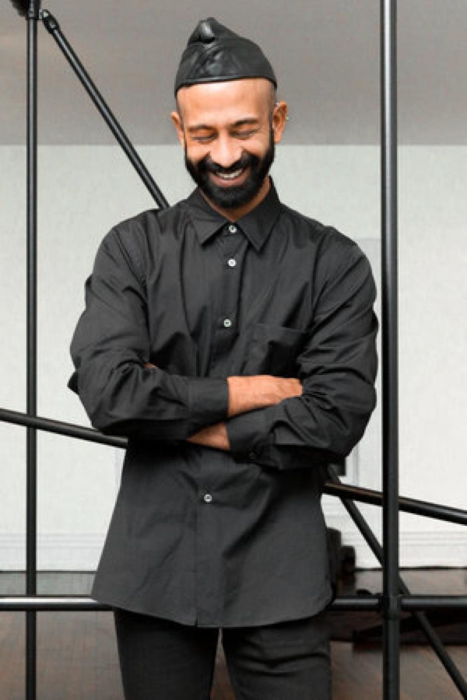 Photo of program faculty, Brendan Fernandes, looking down with arms folded, laughing