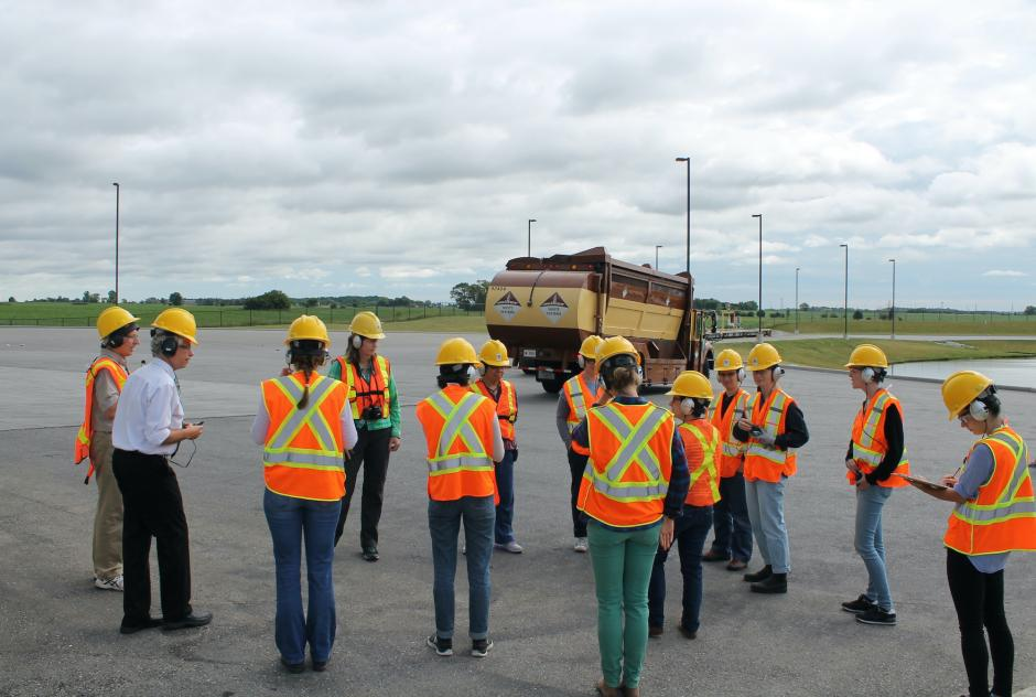 Photograph of twelve people wearing safety gear standing in a loose circle on a large concrete lot. There is a city garbage truck in the background.