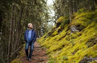 Artist Joel Ivany walking through a lush forest.