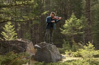 Musician Barry Shiffman standing on a rock in nature playing violin.