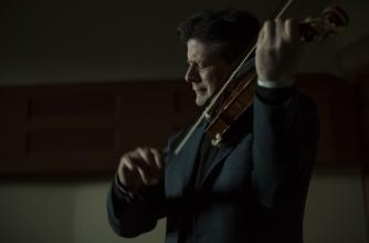 Barry Shiffman playing the violin in a dark theatre.