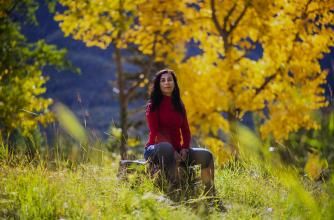Artist Carmen Aguirre poses in a colourful forest in the fall.